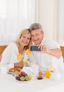 Happy mature couple taking a selfie photo on their mobile phone while having healthy breakfast seated at the table spread with Stock Photo