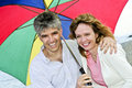 Happy mature couple with umbrella Stock Images