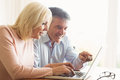Happy mature couple using laptop at home in the kitchen Royalty Free Stock Images