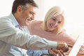 Happy mature couple using laptop at home in the kitchen Stock Photography