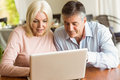 Happy mature couple using laptop at home in the kitchen Royalty Free Stock Photo