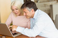 Happy mature couple using laptop at home in the kitchen Royalty Free Stock Photography