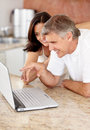 Happy mature couple using laptop in the kitchen Stock Photo