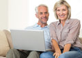 Happy mature couple using laptop on sofa portrait of a at home Royalty Free Stock Photos