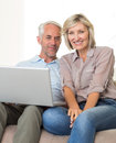 Happy mature couple using laptop on sofa portrait of a at home Royalty Free Stock Image