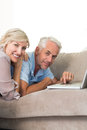 Happy mature couple using laptop on sofa portrait of a at home Stock Photo