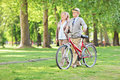 Happy mature couple walking in park and pushing a bike Royalty Free Stock Photos