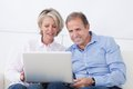 Happy mature couple working on laptop sitting couch and Royalty Free Stock Photography