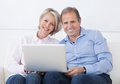 Happy mature couple working on laptop sitting couch and Stock Photo