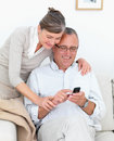 Happy mature couple writing sms together Stock Photos