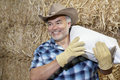 Happy mature cowboy carrying sack on shoulder while looking away Stock Images