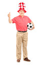 Happy mature fan with hat holding a soccer ball and giving a thu full length portrait of thumb up isolated on white background Royalty Free Stock Photo