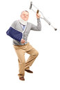 Happy mature gentleman with broken arm holding a crutch Royalty Free Stock Images