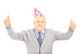 Happy mature gentleman with party hat giving thumbs up isolated on white background Stock Photos