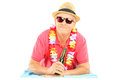 Happy mature man lying on a beach towel and holding a beer with hat sunglasses isolated white background Royalty Free Stock Photo