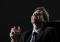 Happy mature man middle aged drinking whiskey against black background Stock Images