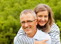 Happy mature man piggybacking his wife Royalty Free Stock Images