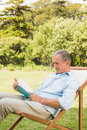 Happy mature man reading book in park sitting on deck chair Stock Photo