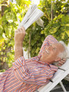 Happy mature man reading newspaper on lounge chair side view of a smiling reclining and Stock Photo