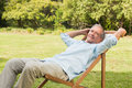 Happy mature man sitting on sun lounger and relaxing in park Royalty Free Stock Photography