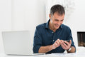 Happy mature man using cellphone smiling in front of laptop Stock Photos