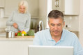Happy mature man using laptop men at home in the kitchen Stock Photos