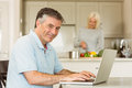 Happy mature man using laptop men at home in the kitchen Stock Photography