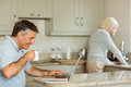 Happy mature man using laptop men at home in the kitchen Stock Photo