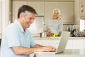 Happy mature man using laptop while wife prepares vegetables men at home in the kitchen Royalty Free Stock Photo