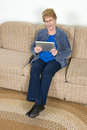 A happy mature senior elderly woman is using an ipad computer and has a smile on her face Royalty Free Stock Photography