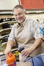 Happy mature store clerk using barcode reader at checkout counter Stock Photos