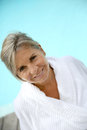 Happy mature woman in bathrobe relaxing near pool portrait of smiling senior sitting by resort Royalty Free Stock Image