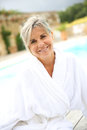 Happy mature woman with bathrobe standing naer pool portrait of smiling senior sitting by resort Stock Photos