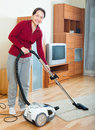 Happy mature woman cleaning with vacuum cleaner on parquet floor Royalty Free Stock Photo