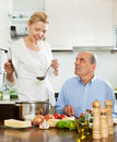 Happy mature woman cooking with husband in kitchen women domestic Royalty Free Stock Photo