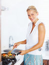 Happy mature woman cooking in the kitchen Royalty Free Stock Photos