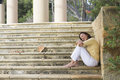Happy mature woman daydreaming closed eyes portrait attractive sitting outdoor on wide limestone steps in park looking relaxed and Stock Photo