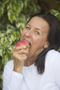 Happy mature woman eating apple portrait beautiful red keeping up nutrition and vitamins healthy and fit blurred background Royalty Free Stock Images