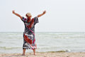 Happy mature woman enjoying breeze on seashore in hat with hands up Stock Images