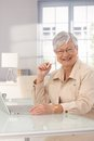 Happy mature woman with laptop sitting at home using computer smiling Royalty Free Stock Photo