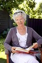 Happy mature woman with novel in garden sitting on a chair a book looking at camera smiling elder reading outdoors Royalty Free Stock Images
