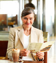 Happy mature woman sitting in a restaurant Royalty Free Stock Photo