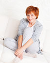 Happy mature woman on sofa female smiling middle at home Stock Images