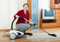 Happy mature woman with vacuum cleaner in living room Royalty Free Stock Photo