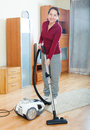 Happy mature woman vacuuming with vacuum cleaner on parquet floor Stock Photography