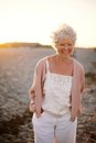 Happy mature woman walking on the beach portrait of beautiful old caucasian lady with smile face outdoors Royalty Free Stock Photos