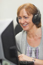 Happy mature woman working on computer while listening to music Stock Photography