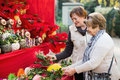 Happy mature women selecting floral compositions
