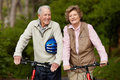 Happy matured couple walking with bicycle Royalty Free Stock Image
