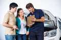 Happy mechanic explaining documents to couple male in auto repair shop Royalty Free Stock Images